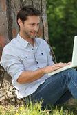 Człowiek siedzi przed drzewem — Zdjęcie stockowe