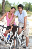 Man and woman biking together — Foto Stock