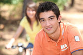 Young riding bikes in the forest — Stockfoto
