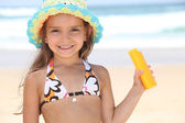 Young girl on the beach holding suncream — Stock Photo