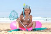 Holčička na pláži s sedí na bóje s potápěním — Stock fotografie