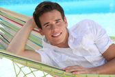 Uomo di cui amaca fronte piscina — Foto Stock