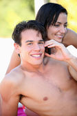 Bare-chested boy phoning with girlfriend by his side — Stock Photo