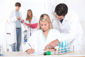 Teacher assisting pupils in science class — Stock Photo