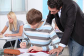 A teacher overlooking the work of one of his pupils in a classroom. — Stock Photo