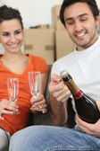 Couple opening bottle of champagne — Stock Photo