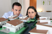 Couple looking at a model of a housing estate — Stock Photo