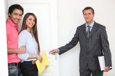 Estate-agent showing couple around property — Stock Photo