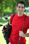 Golfer carrying clubs. — Stock Photo