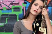 Jovem mulher com guitarra na frente de uma parede de graffiti — Fotografia Stock