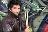 Musician with drumsticks against graffiti wall — Stock Photo