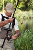 Man watching his fishing rod in front of a river — Stock Photo