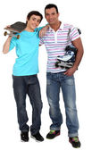 Man with rollerblades and teen carrying skateboard — Stock Photo