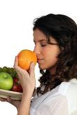 Woman sniffing orange — Stock Photo