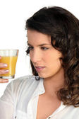 Woman observing orange juice — Stock Photo