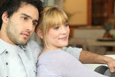 Young couple watching TV at home — Stockfoto