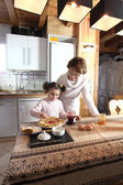 Little girl and grandmother preparing pancakes — Stock Photo
