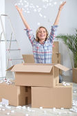 Woman joyously unpacking boxes — Stock Photo