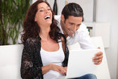 Couple laughing at their laptop — Stock Photo
