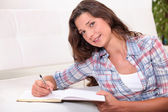 Young woman writing on a notebook on a white bench — Stock Photo