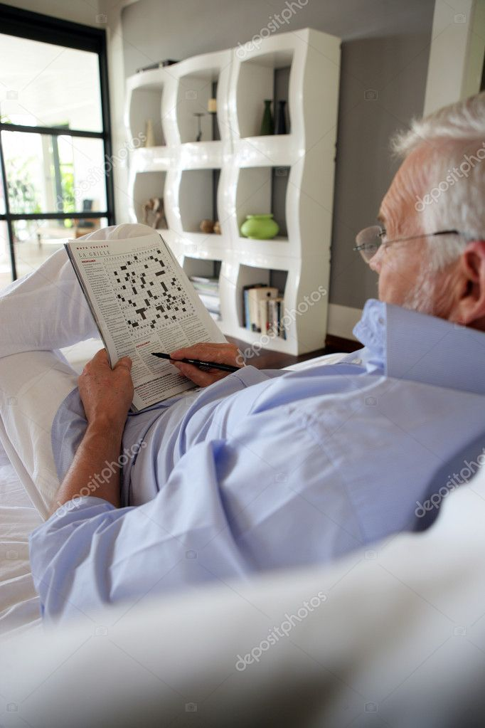 Senior doing a crossword in a magazine  Stock Photo #7915782