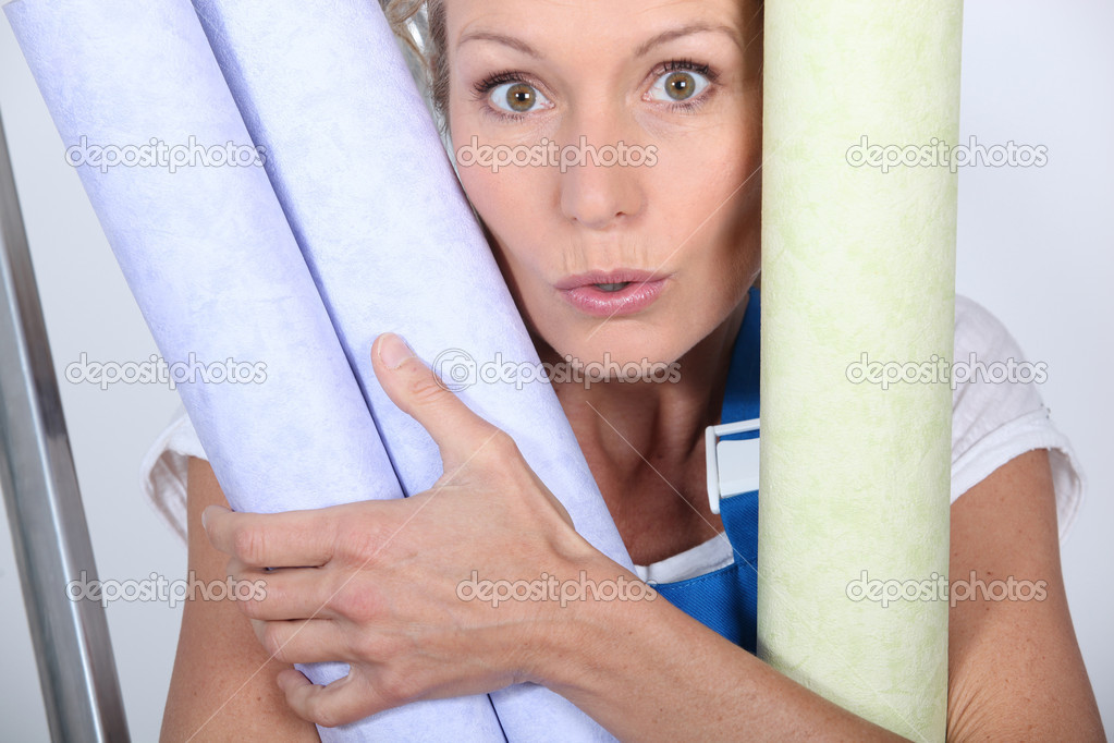 Closeup of woman with rolls of wallpaper — Stock Photo #7919387