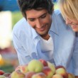 Young couple buying fruit at a market — Stock Photo