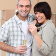 Couple drinking champagne in front of a pile of cardboard boxes — Stock Photo
