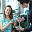 A young female passenger showing her card to a controller on a bus or a tra — Stockfoto