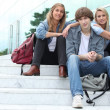Three students sitting outside on some steps - Stock Photo