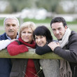 Family leaning against fence - Stock Photo