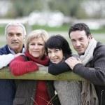 familia apoyado contra la valla — Foto de Stock