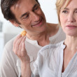 Woman in kitchen holding food in hand man looking at her — Stock Photo