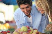 Pareja joven comprando fruta en el mercado — Foto de Stock
