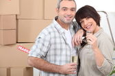 Moving day for a couple celebrating with champagne — Stock Photo