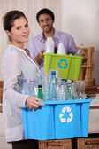 Young couple at home holding crates of plastic bottles — Stock Photo
