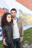 Fashionable young couple stood by wall — Stock Photo