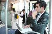 Commuter on a bus with a laptop — 图库照片