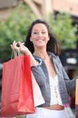 Smiling woman laden down with store bags — Stock Photo