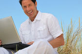 Man smiling on laptop in blue sky — Stock Photo