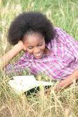 Femme lisant un livre amusant dans un champ — Photo