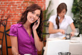 Young woman on cellphone in a restaurant — Stock Photo