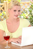 30 years old blonde woman doing computer on a terrace, there's a wine — Stock Photo