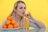 Woman drinking orange juice — Stock Photo