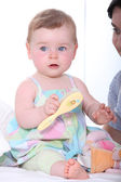 Baby girl with hairbrush — Stock Photo