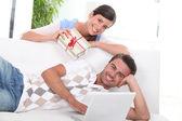 Woman handing gift to man on sofa — Stock Photo