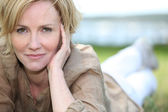 Portrait of magnificent mature blonde lying on grass — Stockfoto