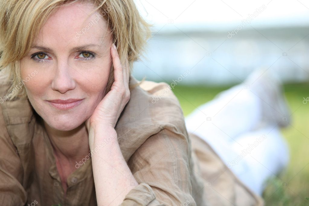 Portrait of magnificent mature blonde lying on grass — Stock Photo #7929892