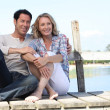 Couple sitting by a lake — Stock Photo #7930420