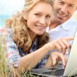 Couple looking at laptop outdoors. — Stock Photo #7930528